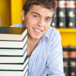 Student With Stacked Books Smiling At Table In Library — Lizenzfreies Foto