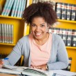 Stock Photo: Female Student With Books Sitting At Table In Library