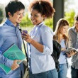 Stock Photo: Happy Friends With Mobilephone And Book In Campus