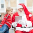 Santa Claus Showing Digital Tablet To Boy — Stockfoto