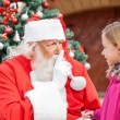 Santa Claus Gesturing Finger On Lips While Looking At Girl — Stock Photo