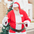 Stock Photo: Santa Claus With Cookies And Milk