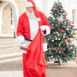Santa Claus Putting Present In Bag — Stock Photo