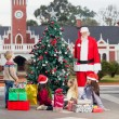 Santa Claus And Children By Decorated Christmas Tree — Foto de Stock