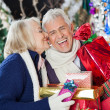 Woman Kissing Happy Man With Christmas Presents — Stock Photo