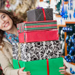 Happy Woman Carrying Stacked Gift Boxes In Store — Stok fotoğraf