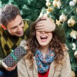 Man Surprising Woman With Gift In Christmas Store — Stock Photo