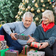 Couple With Presents Sitting In Christmas Store — Stock Photo