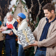 Man Looking At Christmas Present With Family In Background — Stock Photo