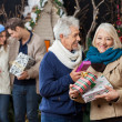 Senior Couple Holding Christmas Presents With Children In Backgr — Stock Photo #35909493