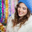 Young Woman Choosing Tinsels At Store — Stock fotografie
