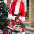 Santa Claus Looking At Children Opening Christmas Presents — Stockfoto