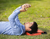 Man Using Mobilephone While Lying On Grass At Campus — Stock Photo
