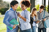 Happy Friends With Mobilephone And Book In Campus — Stock Photo