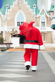 Santa Claus Carrying Bag While Walking In Courtyard — 图库照片