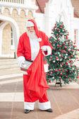 Papai Noel colocando presentes no saco — Fotografia Stock