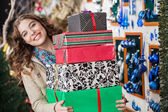 Happy Woman Carrying Stacked Gift Boxes In Store — Stock Photo
