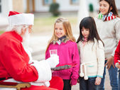Santa Claus Offering Biscuits And Milk To Children — Stock Photo