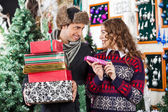 Pár s vánoční dárky v obchodě — Stock fotografie