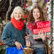 Happy Mother And Daughter With Christmas Presents In Store — Stock Photo