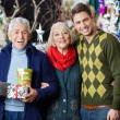 Happy Parents And Son With Presents Standing In Store — Stock Photo