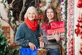 Felice madre e figlia con natale presenta in negozio — Foto Stock