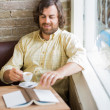 Man With Coffee Cup And Book In Cafeteria — Stock Photo