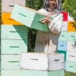 Stock Photo: Beekeeper Carrying Honeycomb Box At Apiary