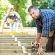 Carpenter Holding Drill At Construction Site — Stock Photo