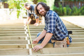 Carpenter Measuring Wood With Tape While Coworker Assisting Him — Stock Photo