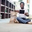 Smiling Student With Books Showing Digital Tablet In Library — Stock Photo