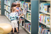 Teacher With Children Selecting Book In Library — Stock Photo