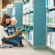 Happy Boy And Teacher Reading Book In Library — Stock Photo #36152697
