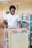 Librarian With Trolley Of Books In Library — Stockfoto