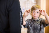 Boy Holding Spectacles With Mother In Foreground At Shop — Stock Photo