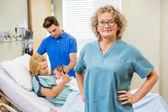 Mature Nurse Standing With Couple And Newborn Baby In Background — Stock Photo