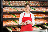 Happy Saleswoman Holding Meat Packages At Counter — Stock Photo