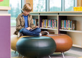 Schoolboy Using Digital Tablet In Library — Stock Photo