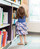 Girl Selecting Book In Library — Stock Photo