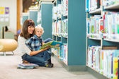 Happy Boy And Teacher Reading Book In Library — Stock Photo
