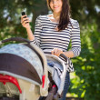 Beautiful Woman With Baby Carriage Using Cell Phone In Park — Stock Photo #36269599