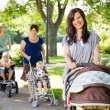 Beautiful Mother Pushing Baby Stroller In Park — Stock Photo #36316767