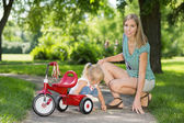 Mother With Daughter Crouching By Tricycle On Walkway — Stok fotoğraf