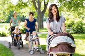 Beautiful Mother Pushing Baby Stroller In Park — Stock Photo