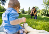 Woman Photographing Baby Boy In Park — Stock Photo
