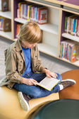 Boy Reading Book In School Library — Stockfoto