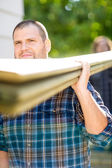 Carpenter Carrying Wooden Planks Outdoors — Stock Photo