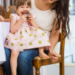Girl Eating Cupcake While Sitting On Mother's Lap — Stock Photo #36622537