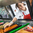Saleswoman Picking Meat Displayed In Cabinet — Stock Photo #36622881