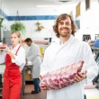 Portrait Of Happy Butcher Holding Meat Package — Stock Photo #36623689